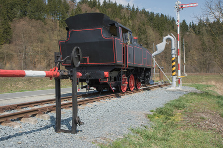 The old steam locomotive is parked on track. All potential trademarks are removed.
