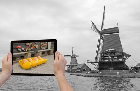 In the bottom left of the photo are hands holding tablet, whose screen contains color photo of the yellow clogs.   photo
