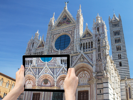 whose: In the bottom left of the photo are hands holding tablet, whose screen contains closeup photo of the cathedral.