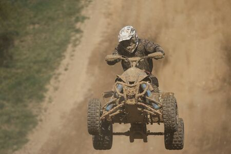 Front view of guad racer jumping. The quad bike and rider are very muddy.Potential trademarks are removed and face of the racer is unidentifiable. photo