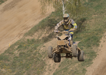 Quad racer is high jumping. The quad bike and rider are very muddy.Potential trademarks are removed and face of the racer is unidentifiable. photo