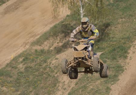 Quad Racer ist Hochsprung. Die Quad-Bike und Fahrer sind sehr muddy.Potential Marken entfernt werden und das Gesicht des Rennfahrers ist nicht identifizierbar. Standard-Bild - 39392795