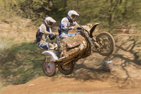 sidecar: MOHELNICE, CZECH REPUBLIC - APRIL 25. Two racers are jumping a sidecar in the International Championship of Czech Republic in sidecarcross 2015 on April 25. 2015 in Mohelnice.