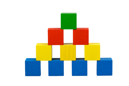 Pyramid built from wooden colorful cubes with gubs isolated on a white background. Bottom line consists of blue cubes over which there are three yellow cubes over which there are two red cubes on top is green cube. Stock Photo