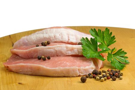 belly pepper: Three sliced pork on a wooden board. Garnished with parsley leaf. Allspice and pepper on a plate. Isolated on the white background