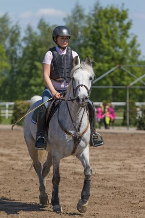 the protector: TRESTINA, CZECH REPUBLIC - MAY 16: Young horsewoman with back protector  is preparing to race at Equestrian Hobby Series 2015 on May 16, 2015  in Trestina, Czech Republic.