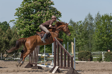 horseman: TRESTINA, CZECH REPUBLIC - MAY 16: Side view of jumping color-matched horseman and brown at Equestrian Hobby Series 2015 on May 16, 2015  in Trestina, Czech Republic.