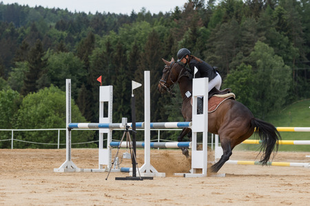 refused: SVEBOHOV, CZECH REPUBLIC - MAY 23: Young horsewoman is mastering a brown horse who refused to jump an obstacle jumping at Summer Jumping Event  2015 on May 23, 2015  in Svebohov, Czech Republic. Editorial