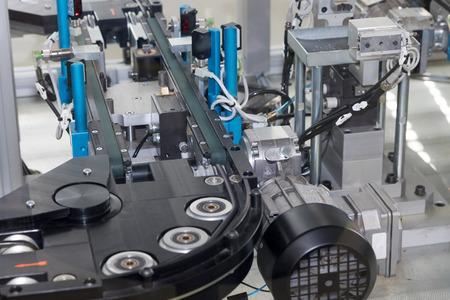 mecanica industrial: Vista detallada de una l�nea de montaje vac�o para la producci�n de componentes de pl�stico. Horizontalmente. Se eliminan todas las marcas posibles.