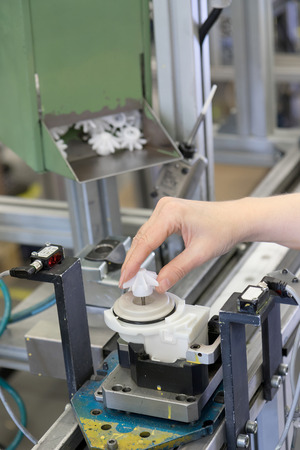 movable: Hand of woman worker is deploying movable element on the plastic component on the assembly line. Vertically. All porential trademarks are removed