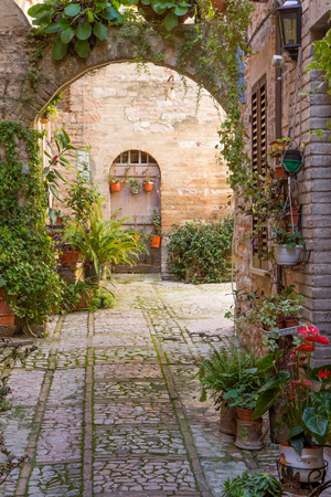 spello: Romantic stone arch decorated with plants and flowers (Spello, Umbria, Italy.)