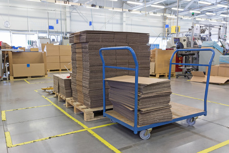 packaging: Cardboard boxes are folded in a designated place in the assembly hall. The show of lean management. All potential trademarks are removed. Stock Photo