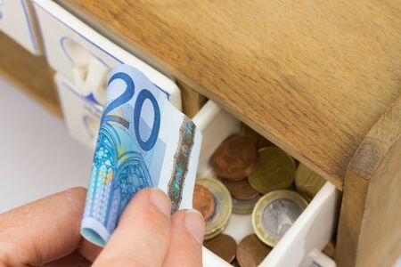 twenty euro banknote: Hand is inserting twenty euro banknote in the box for spices. Euro coins are inside the box for the spices.