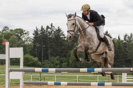"""uomo a cavallo: Svébohov, REPUBBLICA CECA - 23 maggio: vista laterale del primo piano di cavaliere in giacca nera su un cavallo bianco che salta alla """"Summer Jumping Event 2015"""" il 23 maggio 2015 a Svébohov, Repubblica Ceca."""