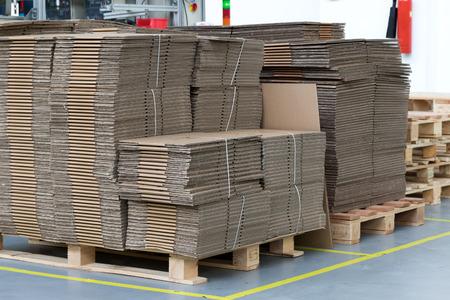Groot aantal gevouwen kartonnen dozen zijn opgemaakt in een aangewezen plaats in de aula. Verticaal. Alle potentiële handelsmerken zijn verwijderd. Stockfoto