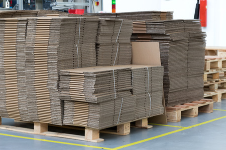 assembly hall: Large number of folded cardboard boxes are made up in a designated place in the assembly hall. Vertically. All potential trademarks are removed. Stock Photo