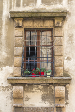 grates: Medieval window with its solid metal grates and pots with flowers Stock Photo
