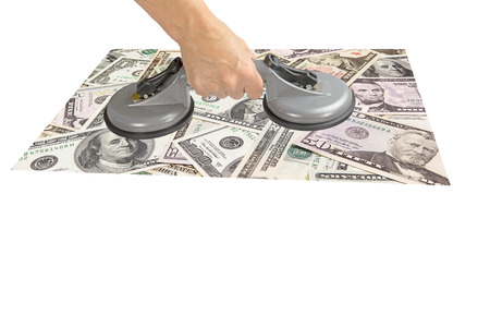suction: Female hand is holding the grey Dual Cup Suction Lifter, on which are attached US dollar banknotes. All is isolated on the white background.