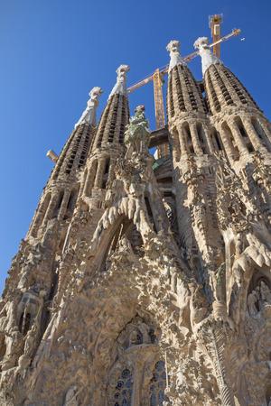 barcelone: Tours de la célèbre église de la Sagrada Familia à Barcelone (Catalogne, Espagne). Bleu ciel et les grues dans le fond.