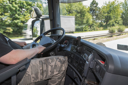 truck driver: View from the truck cab for the driver who holds the steering wheel. White truck is passing  in the opposite. All potential trademarks are removed.