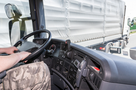 overtaken: View from the truck cab for the driver who holds the steering wheel. The truck is just overtaken by another truck. All potential trademarks are removed. Stock Photo