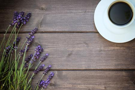 espliego: Flores de lavanda se colocan sobre una tabla de madera. Lugar libre para el texto está en el centro de la foto. La taza de café negro se encuentra en la esquina superior derecha de la foto. La foto se editó como la vendimia con bordes deliberadamente oscuros.