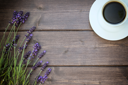 edited photo: Lavender flowers are laid on a wooden board. Free place for your text is in the centre of the photo. The cup of black coffee is  in the top right corner of the photo. The photo is edited as a vintage with deliberately dark edges.