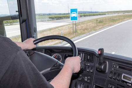 truck driver: View from the truck cab for the driver who holds the steering wheel. Blue sign is visible from the cab of the vehicle. All potential trademarks are removed.