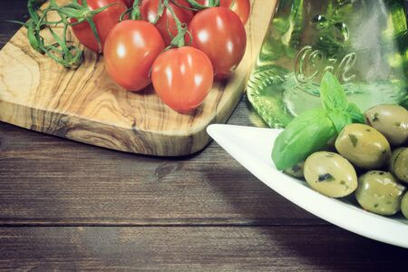 edited photo: White bowl with marinated green olives is placed on a wooden desk. Tomatoes are lying on a desk of olive wood. Bottle with oil is standing in the background. Edited as a vintage photo with darken edges. Stock Photo