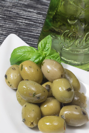 placemats: White bowl with marinated green olives garnished with basil leaves  is placed on a black and white placemats.  Bottle with oil is standing in the background. Vertically.