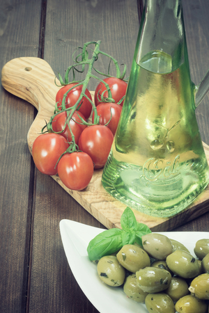 darken: White bowl with marinated green olives is placed on a wooden desk. Tomatoes and bottle of oil are lying on a desk of olive wood. Edited as a vintage photo with darken edges. Stock Photo