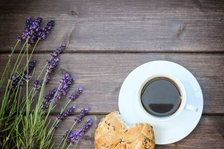 deliberately: Lavender flowers are laid on a wooden board. The cup of black coffee with eaten bread is  in the botton of the photo. The photo is edited as a vintage with deliberately dark edges.