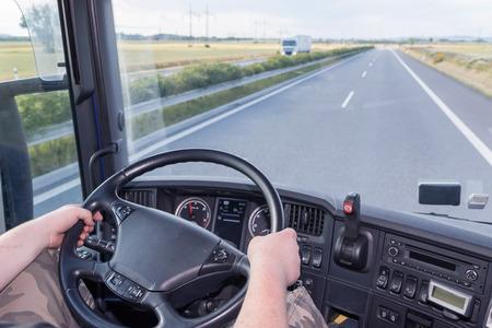 ciężarówka: Kierowca trzyma kierownicę i jedzie ciężarówka na autostradzie. Pusta droga jest przed nim. Biały ciężarówka jedzie w przeciwnym kierunku.