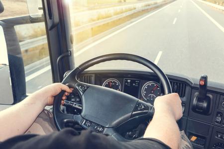 cabaña: Ver en el salpicadero de la conducción de camiones. El conductor está sosteniendo el volante. Carretera vacía está delante del coche. Lente editados como efecto Instagram y usados ??bengala efecto.