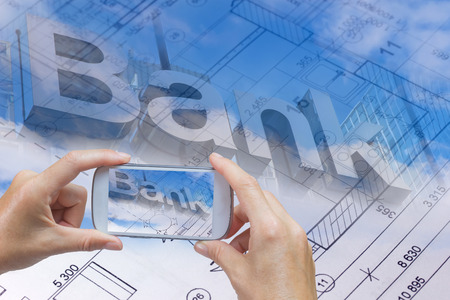 cell phone: In the bottom left of the photo are hands holding smart phone, whose screen contains photo of the bank inscription. Background of the photo contains abstract of the blueprint and bank inscription on the blue sky with clouds. Stock Photo
