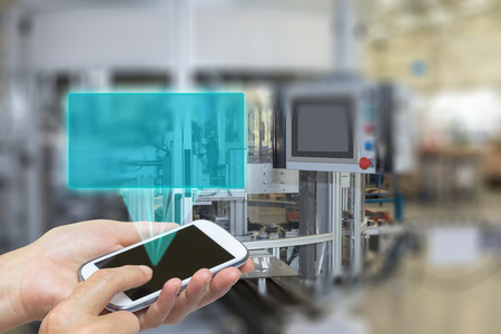 factory line: Female is using the smart phone Blank transparent rectangle radiates from the screen smart phone. The rectangle is ready for your text. The automatic production line is in the background. The edges of the pictures are deliberately blurred. Stock Photo