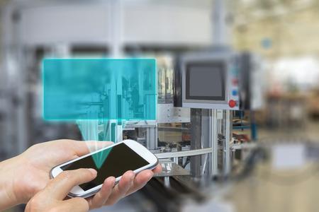 Mujer está utilizando el teléfono inteligente en blanco rectángulo transparente irradia desde el teléfono inteligente de pantalla. El rectángulo está listo para su texto. La línea de producción automática es en el fondo. Los bordes de las imágenes son deliberadamente borrosa. Foto de archivo