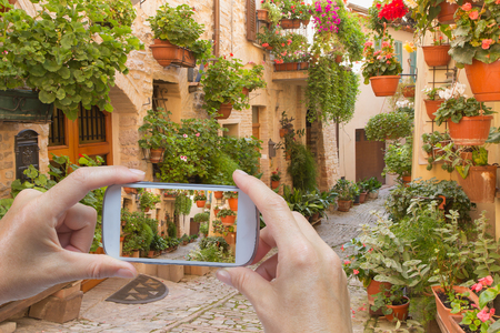 spello: In the bottom left of the photo are hands holding smart phone, whose screen contains photo of the flower street in the town of Spello in Italy. Background of the photo contains also the street of Spello.