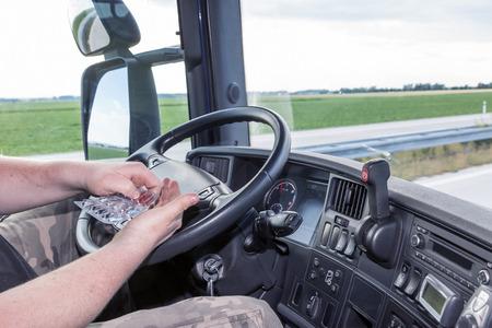 운전자는 트럭을 운전하는 동안 piil를 사용합니다. 트럭 택시 내부에서보기.