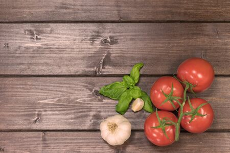 talian: Tomatoes, garlic and basil leaves are lying on a wooden board in the bottom right corner of the photo. Photo is edited as vintage photo. Photo is edited with sunlight filter.