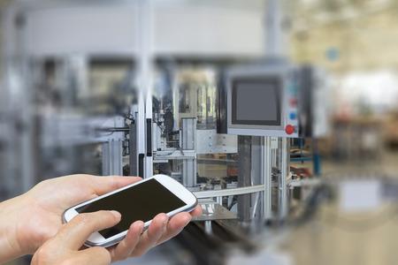Vrouw wordt met behulp van de slimme telefoon. De automatische productielijn is op de achtergrond. De randen van de foto's zijn met opzet vaag.