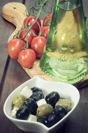 edited photo: White bowl with marinated cheese, black and green olives is placed on a wooden desk. Tomatoes and bottle of oil are lying on a desk of olive wood. Photo is edited as a vintage photo with darken edges.