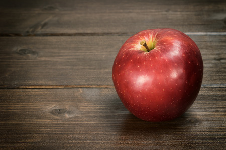 edited photo: The red apple is standing on a wooden table. Photo is edited as a rustic photo with darken edges.
