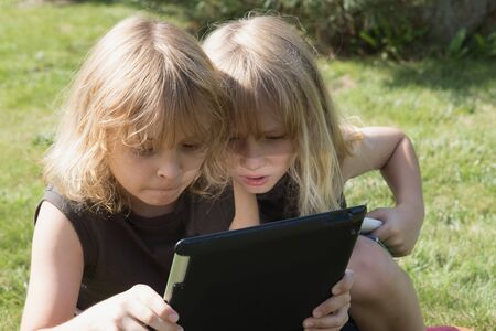 impressed: Two blond brothers are sitting on the grass and looking to the tablet. Boy sitting on the right has an open mouth and is impressed  by what he  see on the tablet. All potentials trademarks are removed,