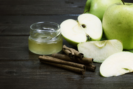 edited photo: Green apples, a jar of honey and a cinnamon are  lying on a wooden table. In the foreground is the apple sliced. Edited as a rustic photo by color splash effect with dark background. Stock Photo