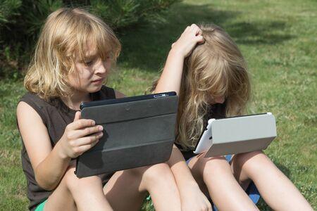 niños rubios: Dos chicos de pelo largo rubio están sentados en el césped y están buscando a la tableta. Ambos muchachos han abierto sus tabletas. Muchacho que se sienta a la derecha se rasca la cabeza con la mano. Se eliminan todas las marcas posibles.