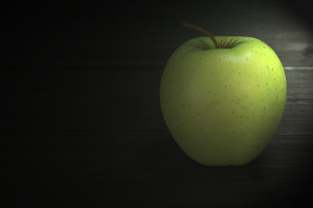 edited photo: Alone green apple is standing on a wooden table. Edited as a rustic photo with dark background. Soft light illuminates the apple from the top right corner of the photo.