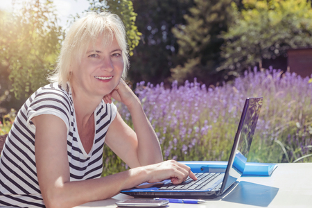 edited photo: Smiling blonde middle aged woman is sitting outdoors with open notebook on the table. Garden with blooming lavender is in the background. Photo is edited like summer photo with light in the upper left corner of the photo.