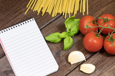 garlic cloves: Blank notebook with lined paper, garlic cloves, basil leaves, spaghetti and tomatoes are lying on the wooden table.