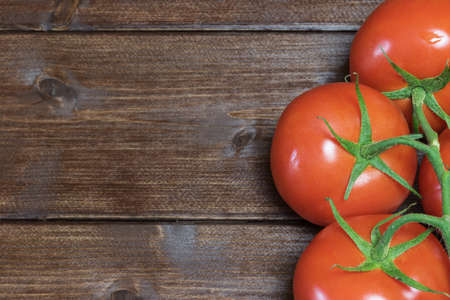 talian: Tomatoes are lying on a wooden board in the right edge of the photo. Stock Photo